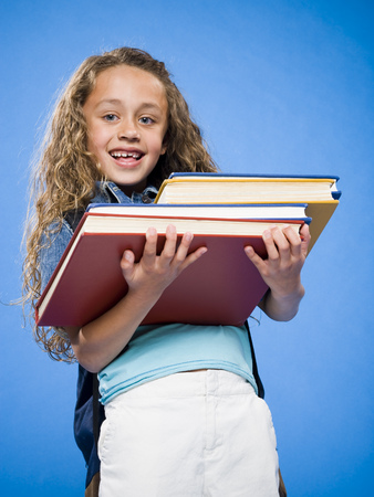 Smiling Girl With Backpack Carrying Pile Of Textbooks LANG_EVOIMAGES