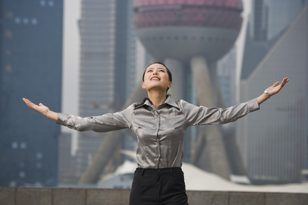 Businesswoman Smiling Outdoors With Arms Up And City Skyline In Background
