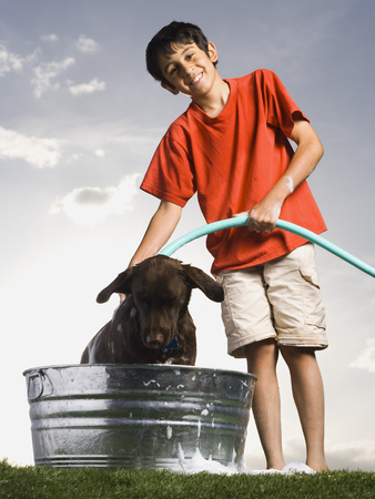 Boy Bathing Dog Outdoors On Cloudy Day Smiling LANG_EVOIMAGES