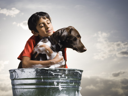 Smiling Boy Hugging And Bathing Dog Outdoors On Cloudy Day LANG_EVOIMAGES