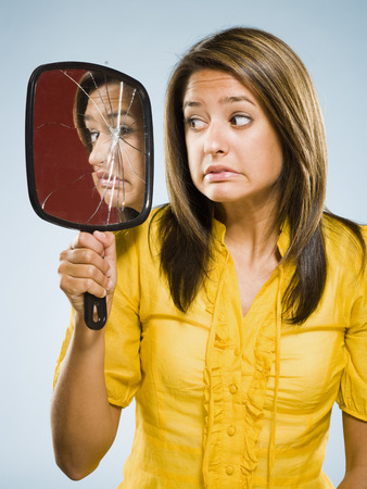 Woman Looking Into Shattered Mirror Nervously LANG_EVOIMAGES