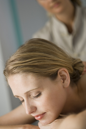 caregivers: Woman With Eyes Closed Getting Massage