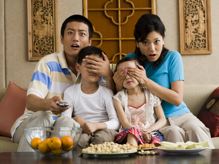 Family Watching Television With Parents Covering ChildrenS Eyes
