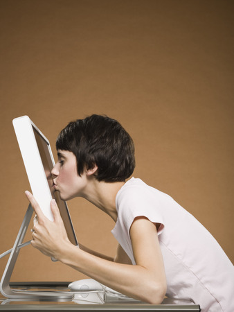 Profile Of Woman Kissing Computer Monitor