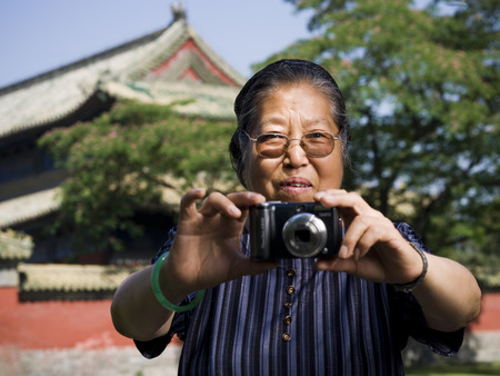 Mature Woman With Camera Outdoors Smiling LANG_EVOIMAGES