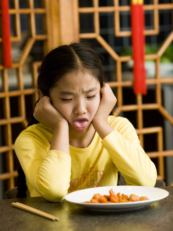 Girl Sitting At Table Looking At Plate Of Food With Disgust