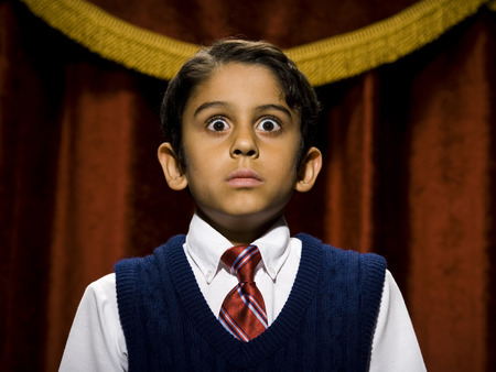 cowering: Boy Standing On Stage With Microphone And Big Eyes