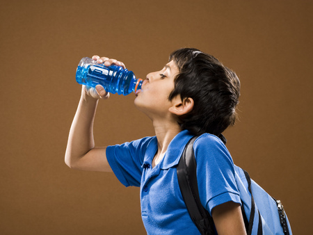 Profile Of Boy With Backpack Drinking Beverage From Plastic Bottle