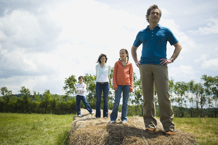 Man And A Woman Standing With Their Children On Hay Bales