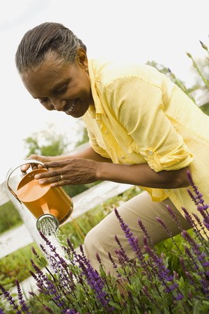 Close-Up Of A Senior Woman Watering Flowers LANG_EVOIMAGES