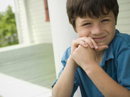 Retrato de un niño con sus manos en su barbilla