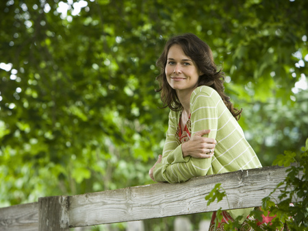 Portrait Of A Woman Leaning On A Wooden Fence LANG_EVOIMAGES