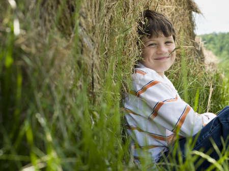 quite: Portrait Of A Boy Sitting Against A Hay Bale