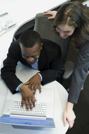 High Angle View Of A Businesswoman And A Businessman Using A Laptop