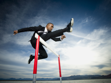 firmeza: Low Angle View Of A Businessman Jumping Over A Hurdle In A Race