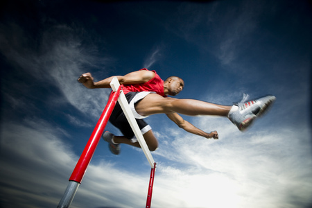 Low Angle View Of A Young Man Jumping Over A Hurdle In A Race LANG_EVOIMAGES