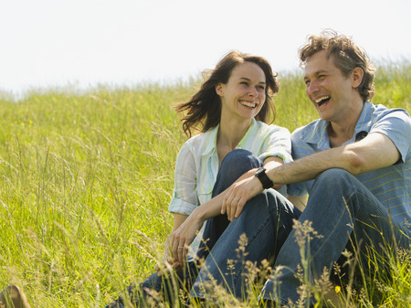 ebullient: Close-Up Of A Woman And A Man Sitting Together And Laughing In A Field