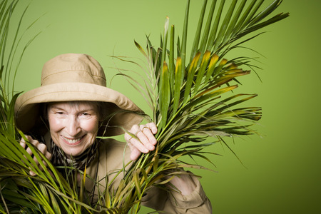 Portrait Of An Elderly Woman Smiling Between Palm Leaves LANG_EVOIMAGES