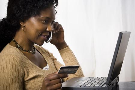 alkalmasság: Profil egy érett nő beszélgetni egy mobiltelefon és Holding a hitelkártya