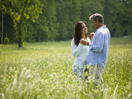 Profile Of A Man And A Woman Holding Hands In A Field LANG_EVOIMAGES