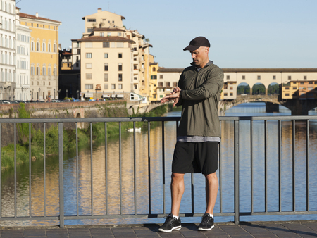 Italy,Florence,Man Checking Time On Bridge Over River Arno