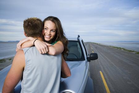 Vista posterior de un hombre adulto medio y una mujer joven abrazándose