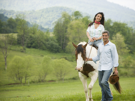 waist down: Woman Riding A Horse With A Man Beside Her