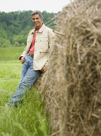 Portrait Of A Man Leaning Against A Hay Bale