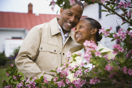 Close-Up Of A Senior Man And A Senior Woman Smiling Behind Flowers LANG_EVOIMAGES