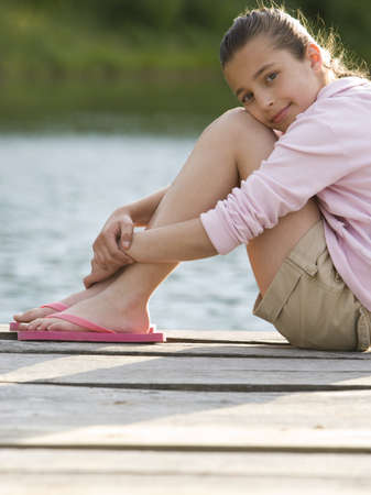Portrait Of A Girl Sitting On A Pier LANG_EVOIMAGES