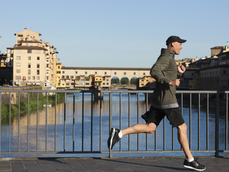 Italy,Florence,Man Jogging Past Ponte Vecchio Over River Arno