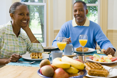 Portrait Of A Senior Man And A Senior Woman Sitting At The Breakfast Table LANG_EVOIMAGES