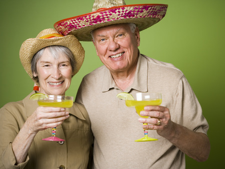 Portrait Of An Elderly Couple Holding Glasses Of Lemon Juice