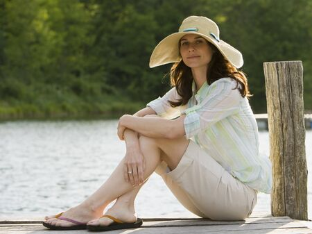 Portrait Of A Woman Wearing A Straw Hat And Sitting On A Pier LANG_EVOIMAGES