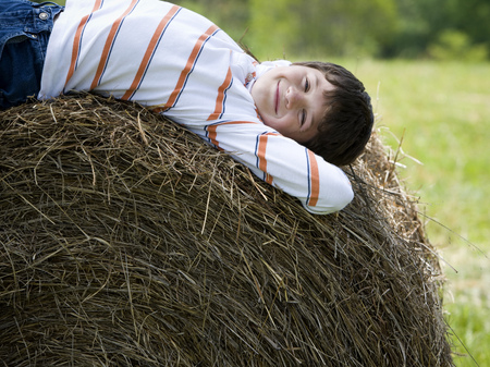 Portrait Of A Boy Lying On A Hay Bale LANG_EVOIMAGES