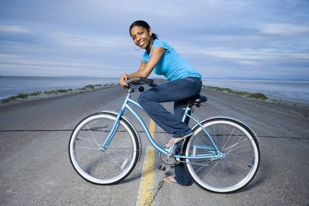 Portrait Of A Young Woman Sitting On A Bicycle