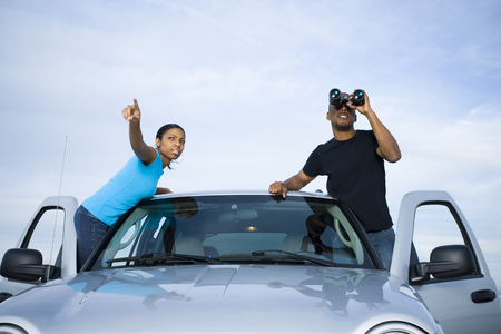 Young Man And A Young Woman Standing Near A Car