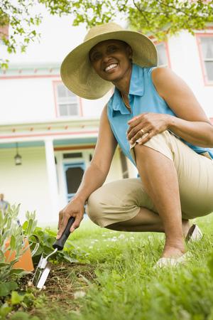 agachado: Senior mujer cavando con una paleta