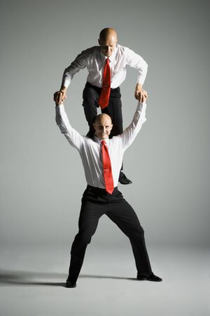 Two Male Acrobats In Business Suits Performing LANG_EVOIMAGES