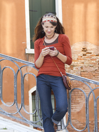 Italy,Venice,Mature Woman Using Electronic Organizer While Leaning Against Railings