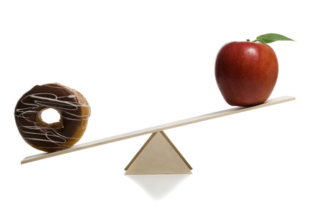 Close-Up Of A Donut And An Apple On A Seesaw