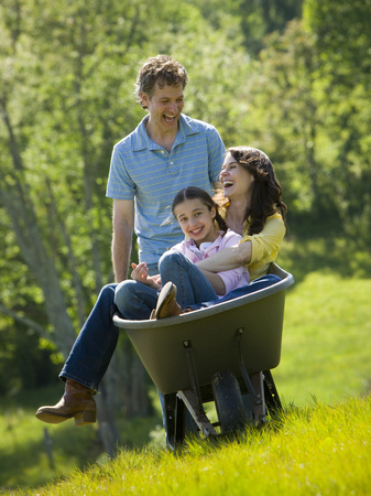 Man Pushing His Daughter And His Wife In A Wheelbarrow