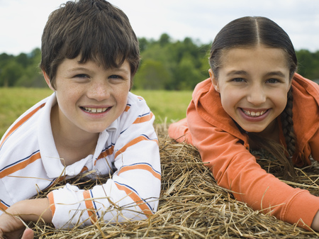 Portrait Of A Boy And A Girl Lying On Top Of A Haystack