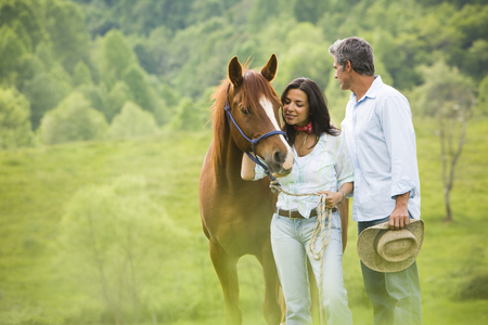 Man And A Woman Standing With A Horse LANG_EVOIMAGES