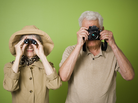 clothe: Close-Up Of An Elderly Woman Looking Through A Pair Of Binoculars With An Elderly Man Taking A Picture