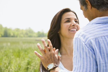 Close-Up Of A Man And A Woman Holding Hands In A Field