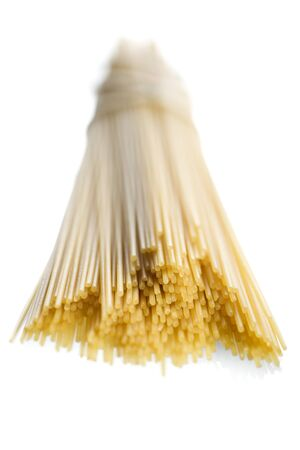 Close-Up Of Uncooked Spaghetti Against A White Background