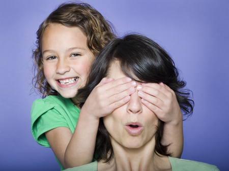 Close-Up Of A Girl Covering Her MotherS Eyes