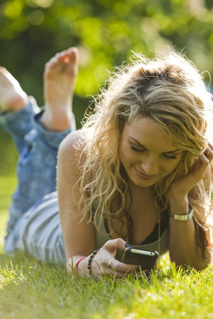Uk,London,Young Woman Lying In Park And Using Mobile Phone