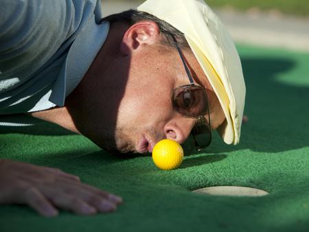 Usa,Utah,Orem,Man Blowing Air To Push Golf Ball LANG_EVOIMAGES